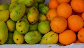 Sweet mango fruits at the rural market. Mango and orange fruits at the rural market in Coron Island, Philippines Royalty Free Stock Photo