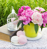 Sweet marshmallows and blooming peonies Stock Photos