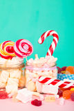 Sweet marshmallows with lollipop. Sweet marshmallows set with lollipop on pastel background with different candies Royalty Free Stock Image