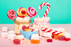 Sweet marshmallows with lollipop. Sweet marshmallows set with lollipop on pastel background with different candies Stock Photo