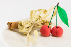 Sweet marzipan cherry fruit with cinnamon spicy stick decoration Royalty Free Stock Photos