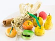Sweet marzipan fruit candies dessert with cinnamon stick decorat Royalty Free Stock Photos