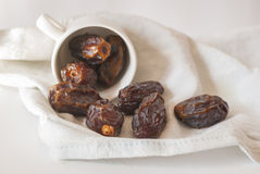 Sweet medjool dates. In a white cup on a fabric; white background Royalty Free Stock Images