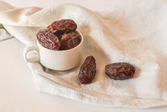 Sweet medjool dates. In a white cup on a fabric; white background Royalty Free Stock Photo
