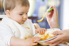 Sweet messy baby boy playing with food while eating. Royalty Free Stock Photos