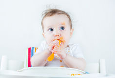 Sweet messy baby eating a carrot in a white high chair Stock Image