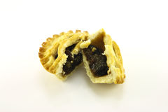 Sweet Mince Pie. Single small sweet mince pie cut in half on a reflective white background Royalty Free Stock Images