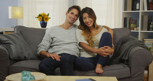Sweet mixed race couple sitting on couch smiling Royalty Free Stock Images