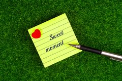 Sweet moment. In memo with heart shape and pen on grass background Stock Photography