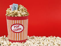 Sweet movie. A popcorn bucket over a red background. Movie stubs sitting over the popcorn Stock Photos
