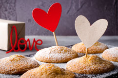 Sweet muffins on dark background with red and kraft paper hearts, for Valentine`s day. Stock Photos