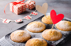 Sweet muffins on dark background with red and kraft paper hearts, for Valentine`s day. Stock Images
