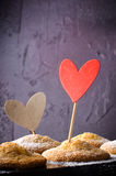 Sweet muffins on dark background with red and kraft paper hearts, for Valentine`s day. Stock Image