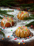 Sweet muffins decorated fondant, multicolored sprinkles. Cupcakes on dark background with spruce branches. Christmas and New Year Royalty Free Stock Photo