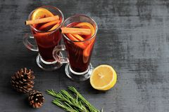 Sweet mulled wine for two person in glasses on a black background, decorated fir cones and rosemary stock images