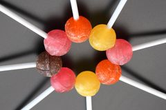 Sweet multicolored caramel on a stick. Sweets laid out on the table stock images
