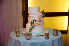 Sweet multilevel wedding cake decorated with pink flowers. Candy bar Royalty Free Stock Photography