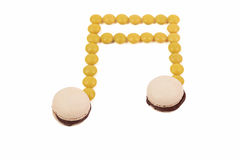 Sweet musical note. Yellow macaron chocolate candy musical note on white background Stock Images