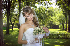 Sweet naughty bride examining her bouquet. Closeup of young naughty bride, examining her bouquet and shaking hands Royalty Free Stock Photography