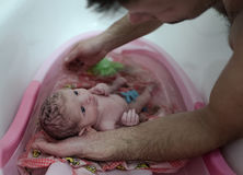 Sweet new born baby son is in father`s arms, bathing Stock Photography