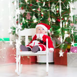 Sweet newborn baby boy in Santa costume under Christmas tree Stock Photos