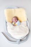 Sweet newborn baby boy in swing on a sheepskin Royalty Free Stock Photography