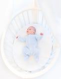 Sweet newborn baby boy in white round crib Royalty Free Stock Photo