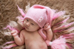 Sweet newborn baby in pink cap open eyes, wakes stock photography