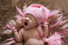 Sweet newborn baby in pink cap yawns and stretches, wakes royalty free stock photography