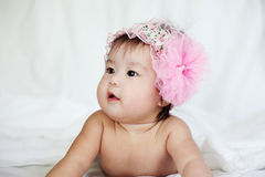 Sweet Newborn Baby in Pink Flower Hairband Lies on Bed Royalty Free Stock Photo