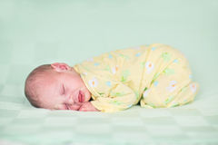 Sweet newborn baby sleeping on green blanket Stock Images