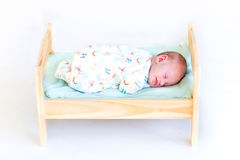 Sweet newborn baby sleeping in toy bed Royalty Free Stock Photography