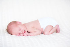 Sweet newborn baby sleeping wearing a diaper Stock Photos