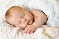 Sweet Newborn Infant Girl Sleeping in White Blankets. A sweet newborn infant girl is sleeping peacefully while snuggled in warm white blankets Stock Image