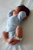 Sweet newborn little baby lying on the bed just two days after arrival Royalty Free Stock Photos