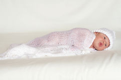 Sweet newborn in white knitted hat Stock Images