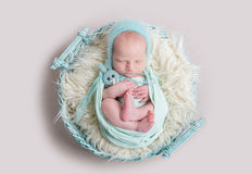 Sweet newborn wrapped in a nappy sleeping on a round rug Royalty Free Stock Images