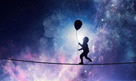 It is sweet night dream. Mixed media. Silhouette of kid boy with balloon against night starry sky. Mixed media Stock Photo