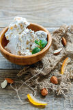 Sweet nougat with almonds and candied fruit in a wooden bowl. Royalty Free Stock Image