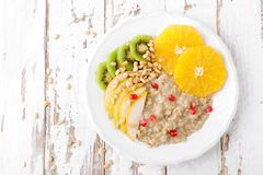 Sweet oatmeal porridge with pine nuts and fresh fruits - pear, orange, kiwi and pomegranate. Healthy dietary breakfast. Vegetarian. Dish. Top view stock photos