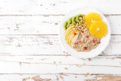 Sweet oatmeal porridge with pine nuts and fresh fruits - pear, orange, kiwi and pomegranate. Healthy dietary breakfast. Vegetarian. Dish. Top view stock images