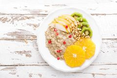 Sweet oatmeal porridge with pine nuts and fresh fruits - pear, orange, kiwi and pomegranate. Healthy dietary breakfast. Vegetarian. Dish. Top view royalty free stock images