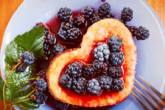 Sweet omelet with blackberries, heart-shaped. Insta-retro photo effect Stock Photography