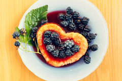 Sweet omelet with blackberries on wooden table. Sweet omelet with blackberries, heart-shaped on wooden table Stock Photography