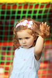 A sweet one year old girl with pink head band with bow and flower in the summer park, hand stuck in long curly hair Stock Photography