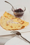 Sweet, organic crepe on a square white plate. Sweet, organic crepe with powdered sugar on a square white plate, with a clear glass bowl of raspberry preserves Stock Photography