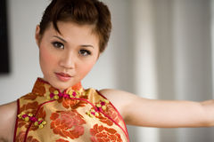 Sweet oriental girl. Beautiful oriental girl smile in a cheongsam Royalty Free Stock Photo