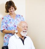 Sweet Pain Relief. Senior man gets pain relief from a chiropractic nurse using an ultrasound machine royalty free stock photo