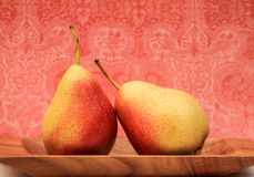 Sweet Pair. Delicious pink-yellow pears on pink swirls background Stock Photography