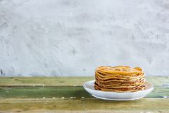 Sweet pancake tower. Sweet breakfast with pancake tower on white plate over wooden table. Concrete background, selective focus Royalty Free Stock Photo